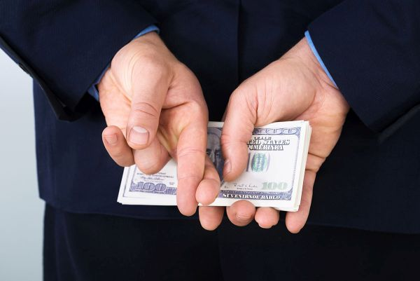 Businessman Standing With Crossed Finger And Holding Banknotes Behind His Back